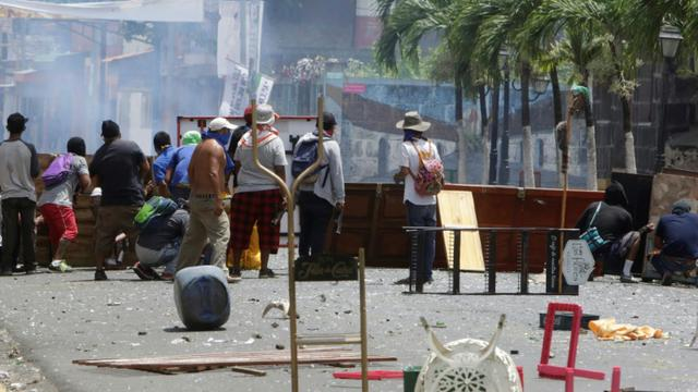 Des manifestants s'abritent derrière des barricades de fortune lors de heurts avec les forces de police, le 2 juin 2018 à Monimbo, près de Masaya, à 40 km de Managua, au Nicaragua [INTI OCON / AFP]