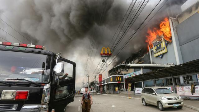 Des pompiers sur les lieux de l'incendie dans un centre commercial à Davao, aux Philippines, le 23 décembre 2017 [MANMAN DEJETO / AFP]