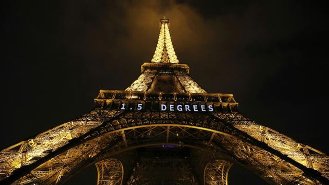 """""""1,5 degré"""" est inscrit en néon blanc sur la Tour Eiffel, le 10 décembre 2015 la veille de la clôture de la COP21 [PATRICK KOVARIK / AFP]"""