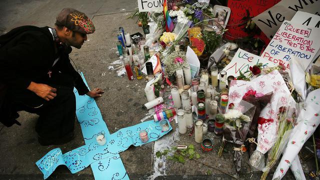 Un homme devant des bougies en mémoire de Mark Carson, victime d'un meurtre homophone, le 22 mai 2013 [Spencer Platt / Getty Images/AFP/Archives]