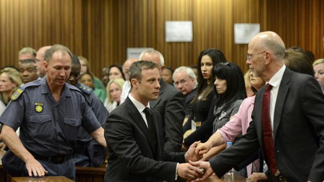 Oscar Pistorius serre la main de son oncle Arnold Pistorius avant d'être emmené en prison à l'issue de son procès le 21 octobre 2014 à Pretoria [Herman Verwey / POOL/AFP/Archives]
