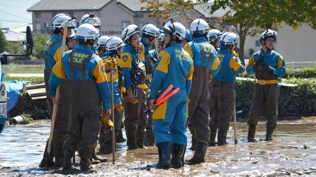 Des policiers à la recherche de disparus lors des inondations le 11 septembre 2015 à Joso au Japon [KAZUHIRO NOGI / AFP]