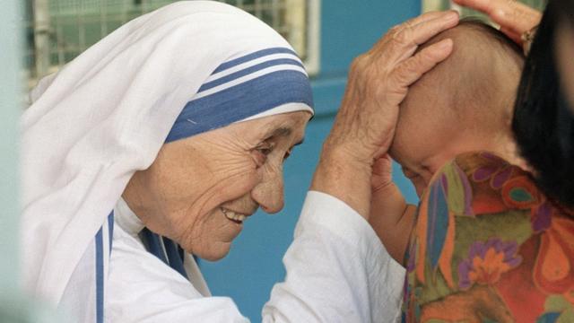 Mère Teresa bénit un enfant à Singapour le 20 octobre 1993 [ROSLAN RAHMAN / AFP/Archives]
