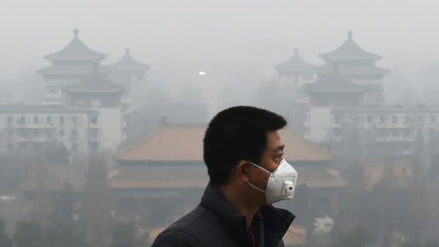 Un homme porte un masque pour se protéger de l'épais brouillard toxique qui submerge Pékin, le 8 décembre 2015 [GREG BAKER / AFP]