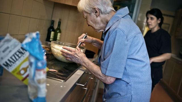 Une personne âgée prépare un gâteau sous l'oeil attentif d'une aide de vie, en Bourgogne en juillet 2011 [Jeff Pachoud / AFP]