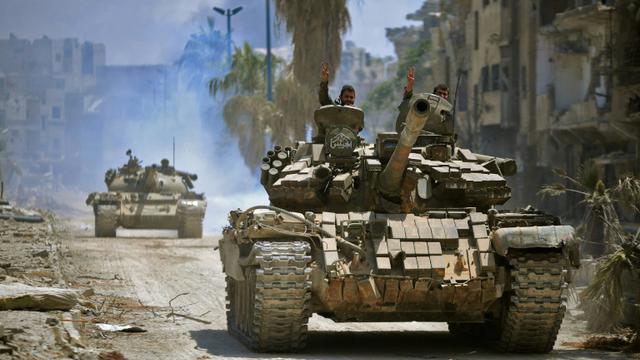 Des combattants gouvernementaux progressent en direction de positions du groupe jihadiste Etat islamique (EI) dans le quartier de Hajar al-Aswad dans le sud de Damas. Photo fournie par l'agence officielle syrienne SANA, le 14 mai 2018 [Handout / SANA/AFP/Archives]