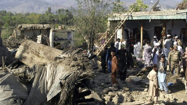 Des policiers et habitants au milieu des ruines de maisons détruites par un puissant séisme, le 27 octobre 2015 à Lower Dir, au Pakistan [EHSAN ULLAH / AFP]