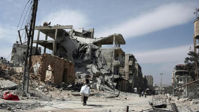 Des Syriens fuyant la localité de Hammouriyé et ses bâtiments détruits par les bombardements face à l'avancée des forces du régime, le 15 mars 2018 [ABDULMONAM EASSA / AFP]
