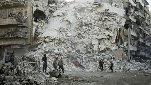 Des membres de forces de défense syrienne cherchent des corps parmi les ruines d'un immeuble à Alep le 17 octobre 2016 [KARAM AL-MASRI / AFP/Archives]