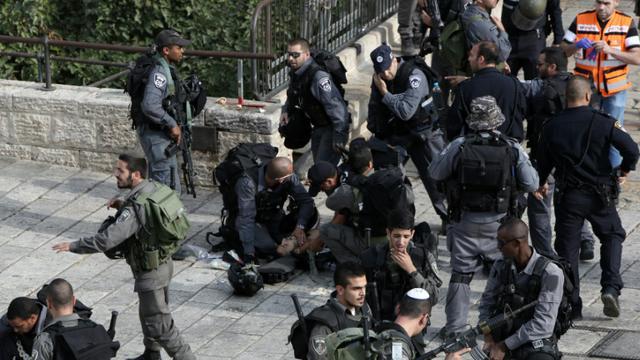 Un policier israélien agressé au couteau par un Palestinien reçoit les premiers soins entouré par ses collèges, le 10 octobre 2015 près de la Vieille ville de Jérusalem [GALI TIBBON / AFP]