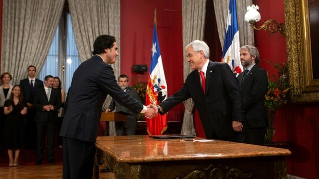 Le ministre des Finances chilien, Ignacio Briones (G) serre la main du président chilien Sebastian Pinera à Santiago du Chili, le 28 octobre 2019 [CLAUDIO REYES / AFP/Archives]
