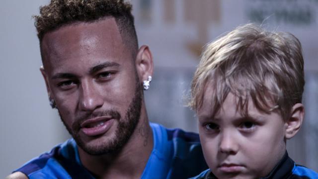 Neymar, avec son fils Davi Lucca, accorde un entretien à l'AFP, le 21 juillet 2018 à Praia Grande, près de Sao Paulo  [Miguel SCHINCARIOL / AFP]