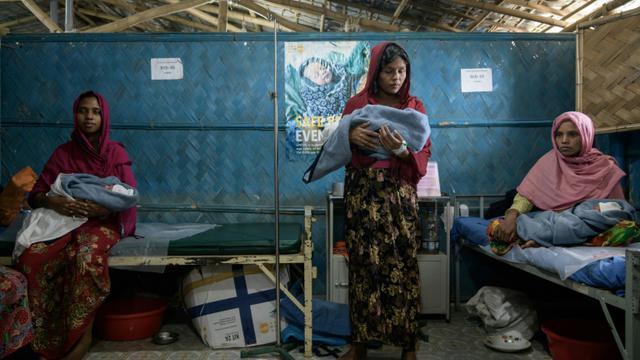 Les réfugiés rohingya Fatena Khatun (g), 20 ans, Zarina Begum (c), 20 ans et Latifa Begum (d), 30 ans, avec leurs bébés nés quelques heures auparavant le 14 août 2018 dans une maternité gérée par une ONG dans le camp de réfugiés de Kutupalong près de Cox's Bazar [Ed JONES / AFP]