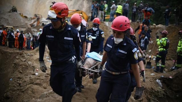 Des pompiers transportent un corps après un glissement de terrin près de Guatemala city le 3 octobre 2015 [JOHAN ORDONEZ / AFP]