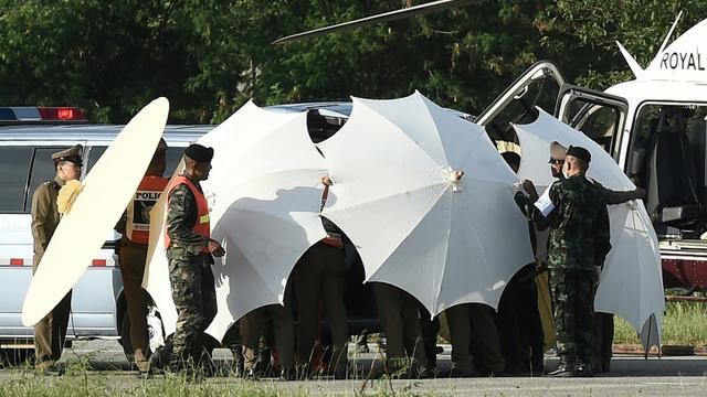 Des policiers et des militaires recouvrent une civière avec des parapluies le 9 juillet 2018 alors que se poursuivent les opérations de sauvetage pour de jeunes footballeurs coincés dans une grotte en Thaïlande  [LILLIAN SUWANRUMPHA                  / AFP/Archives]