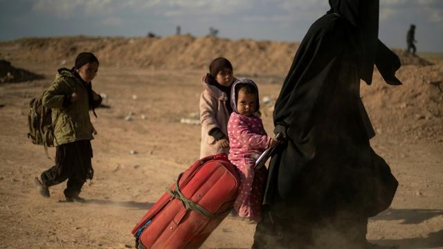Une femme et ses enfants ayant fui le réduit du groupe Etat islamique (EI) dans l'est de la Syrie le 6 mars 2019 [Delil souleiman / AFP]