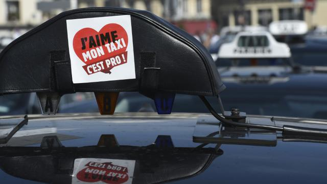 Un sticker a été apposé sur le signe lumineux d'un taxi, pendant une manifestation de chauffeurs de taxi anti-UberPOP, le 25 juin 2015 à Paris [LOIC VENANCE / AFP/Archives]