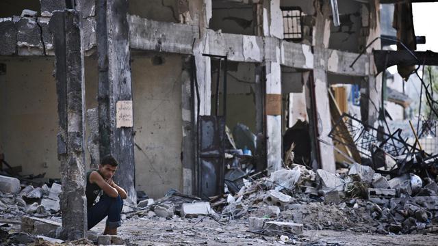 Un Palestinien assis sur des décombres dans la bande de Gaza le 14 août 2014 [Roberto Schmidt / AFP]