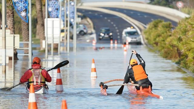 Deux hommes se déplacent en kayak sur une route inondée à Palavas-les-Flots le 23 novembre 2019  [Pascal GUYOT / AFP]