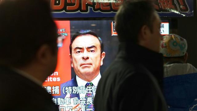 Des piétons passent devant un écran de télévision sur lequel apparaît le visage de Carlos Ghosn, ex-PDG de Nissan, le 21 décembre 2018 à Tokyo, au Japon [Kazuhiro NOGI / AFP/Archives]