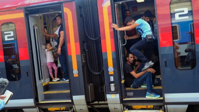 Des migrants montent dans un train en direction de l'Autriche et l'Allemagne, dans la gare de Budapest le 31 août 2015 [ATTILA KISBENEDEK / AFP/Archives]