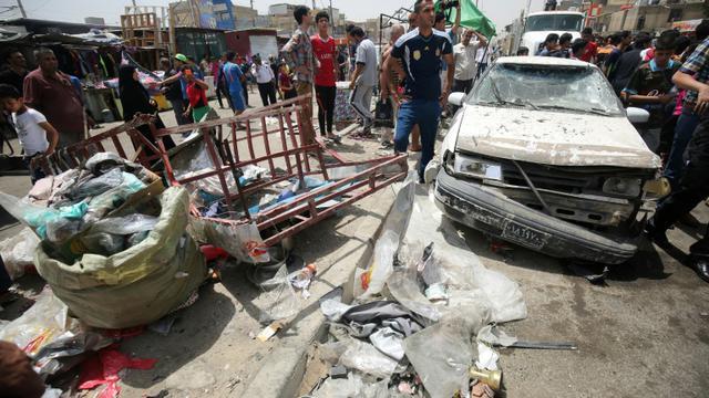 Des passants constatent les dégâts après l'explosion d'une voiture piégée près d'un marché du grand quartier chiite Sadr City, dans le nord de Bagdad le 11 mai 2016 [AHMAD AL-RUBAYE / AFP]