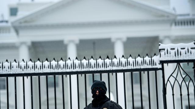 Un membre des services secrets américains devant la Maison Blanche enneigée le dimanche 13 janvier 2019 à Washington [Brendan Smialowski / AFP]