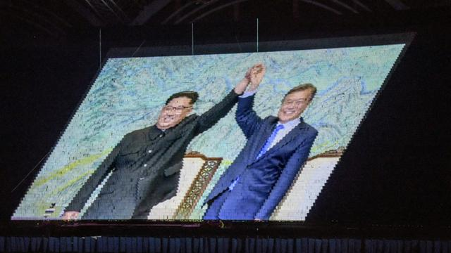 Une image des leaders nord et sud-coréens Kim Jong Un  et Moon-Jae-in est projetée dans un stade de Pyongyang, le 9 septembre 2018. [Ed JONES / AFP]