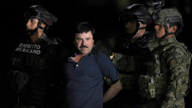 Le baron de la drogue El Chapo maintenu par des policiers peu après son arrestation, le 8 janvier 2016 sur le tarmac de l'aéroport de Mexico [ALFREDO ESTRELLA / AFP]