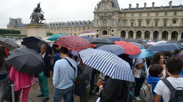 Des visiteurs font la queue sous la pluie devant le musée du Louvre à Paris le 8 août 2014 [Dominique Faget / AFP/Archives]
