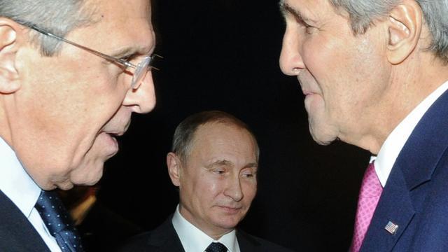 Le ministre russe des Affaires étrangères, Sergueï Lavrov (g) et son homologue américain John Kerry (d) discutent devant le président russe Vladimir Poutine (c), à Paris le 30 novembre 2015 [MIKHAIL KLIMENTYEV / SPUTNIK/AFP/Archives]