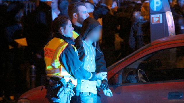 La police arrête un homme parmi ceux rassemblés devant la gare centrale de Cologne, la nuit de la Saint Sylvestre [Markus Boehm / dpa/AFP]