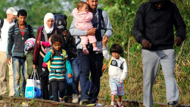 Des familles de migrants à la frontière entre la Serbie et la Hongrie, le 25 août 2015 [ATTILA KISBENEDEK / AFP]
