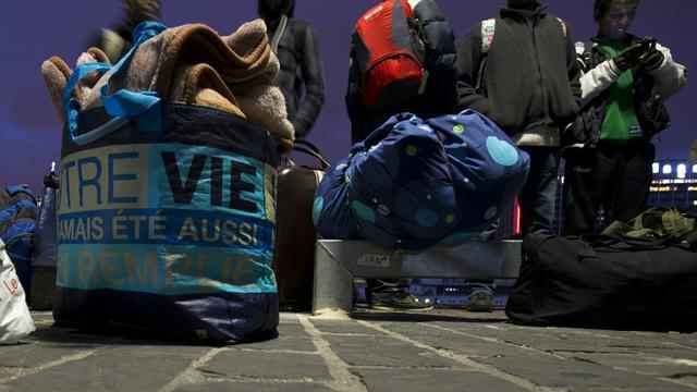 Des migrants ramassent leurs affaires, se préparant à quitter leur camp de fortune près de la gare d'Austerlitz à Paris, le 17 septembre 2015 [JOEL SAGET / AFP/Archives]