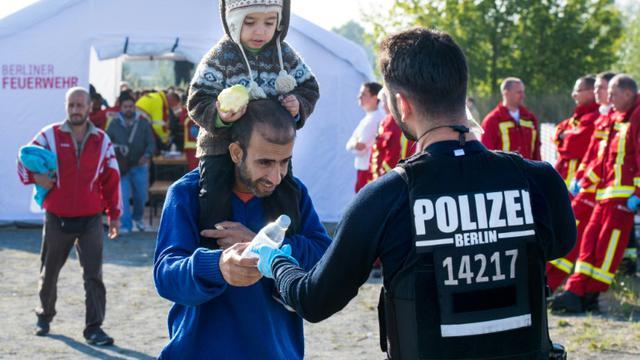 Un policier distibue de l'eau à des migrants à leur arrivée le 10 septembre 2015 à la gare de Schoeneberg près de Berlin [PATRICK PLEUL / DPA/AFP]