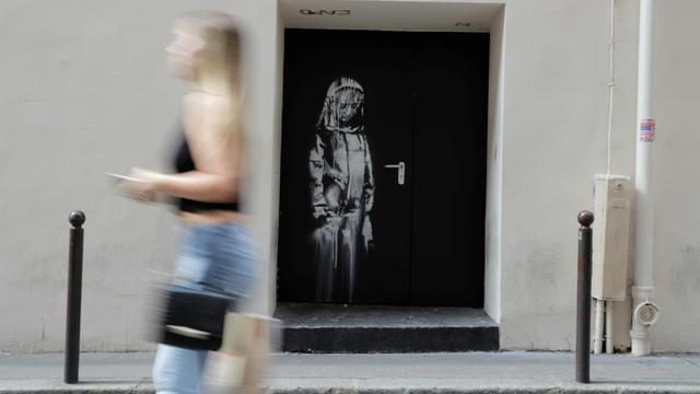 Une femme passe devant le pochoir de l'artiste Bansky le 25 juin 2018, dans une rue près de la salle de concert du Bataclan [Thomas SAMSON / AFP/Archives]
