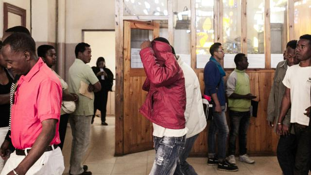 Un accusé cache son visage alors qu'il quitte le tribunal d'Antananarivo, le 9 octobre 2015 [RIJASOLO / AFP]