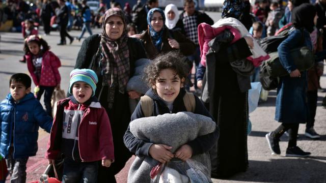 Des réfugiés syriens et irakiens embarquent sur des bus le 23 février 2016 depuis le port du Pirée à Athènes vers la frontière gréco-macédonienne  [LOUISA GOULIAMAKI / AFP]