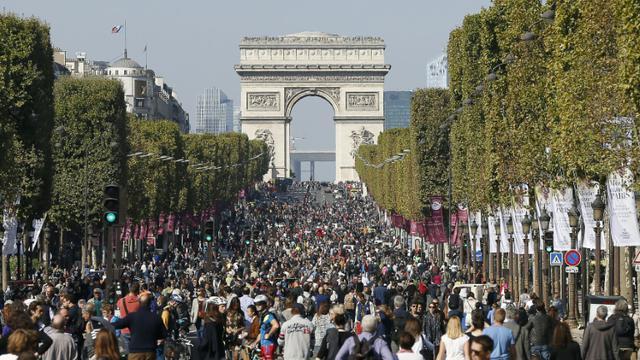 """Des promeneurs et des cyclistes sur les Champs-Elysées pour la première """"journée sans voiture"""" à Paris le 27 septembre 2015 [THOMAS SAMSON / AFP]"""