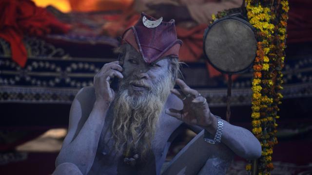 Un ascète hindou téléphone, assis dans sa tente à Allahabad en Inde le 13 janvier 2019, en attendant qu'ouvre le Kumbh Mela, l'un des plus grands rassemblements religieux de la planète [SANJAY KANOJIA / AFP]