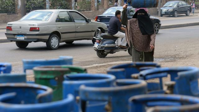 Une femme porte une bouteille de gaz dans les rues du Caire, le 4 avril 2013 [Khaled Desouki / AFP/Archives]