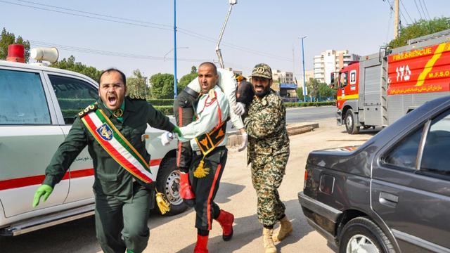 Un homme porte un soldat blessé lors d'une attaque à Ahvaz, dans le sud-ouest de l'Iran, le 22 septembre 2018 [BEHRAD GHASEMI / ISNA/AFP]