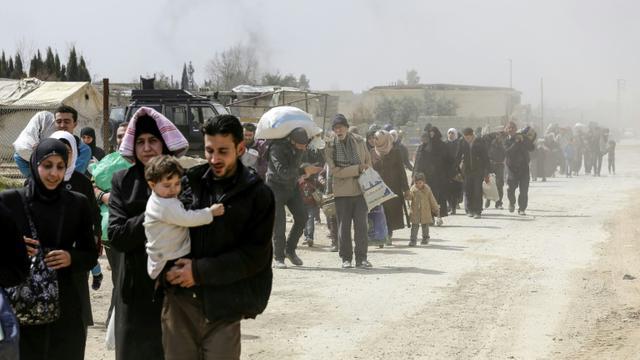 Des civils fuient la région de Hammouriyé dans l'enclave rebelle de la Ghouta orientale, après environ un mois de bombardements du régime syrien, le 15 mars 2018 [LOUAI BESHARA / AFP]