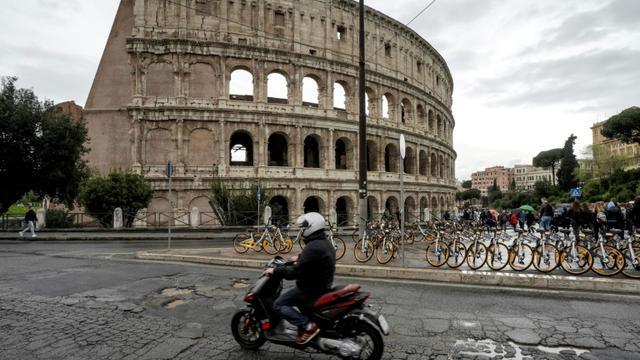 Un motocylciste roule près du Colisée à Rome, le 12 avril 2018  [Andreas SOLARO / AFP]