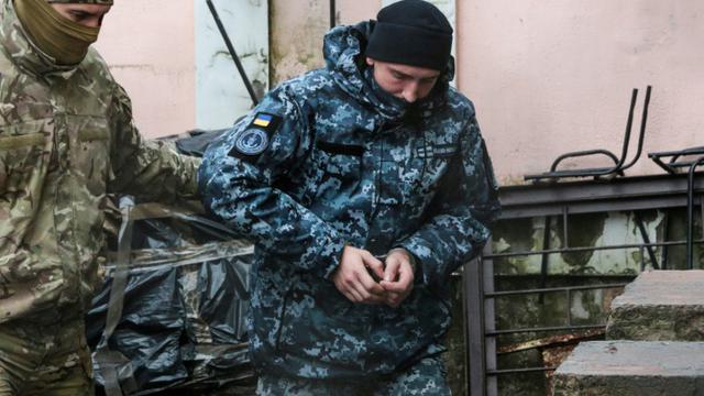 Un marin ukrainien emmené par un agent des services de sécurité russes dans un tribunal en Crimée, le 27 novembre 2018 [STR / AFP]