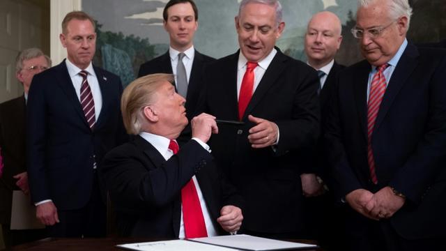 Donald Trump tend son stylo au Premier ministre israélien Benjamin Netanyahu après avoir signé le décret reconnaissant officiellement la souveraineté d'Israël sur le plateau du Golan, le 25 mars 2019 à Washington [SAUL LOEB / AFP]