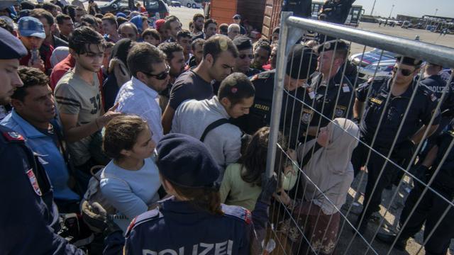 Des policiers autrichiens encadrent des migrants et des réfugiés qui attendent de monter dans des bus, le 12 septembre 2015 près de Nickelsdorf, à la frontière avec la Hongrie [JOE KLAMAR / AFP]