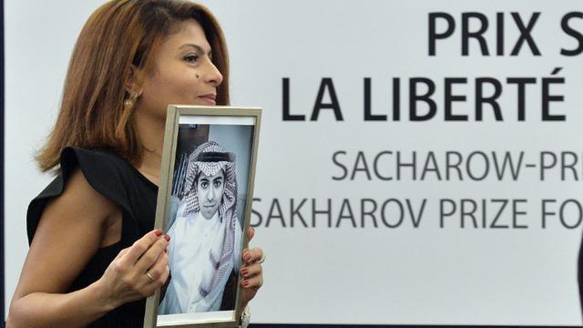 Raef Badaoui tient un portrait de son époux Ensaf Haidar, blogueur saoudien emprisonné, lors de la remise du prix Sakharov à son mari, le 16 décembre 2015 [PATRICK HERTZOG / AFP]