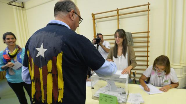 Un homme met un bulletin dans l'urne à Barcelone le 27 septembre 2015 à Barcelone [GERARD JULIEN / AFP]