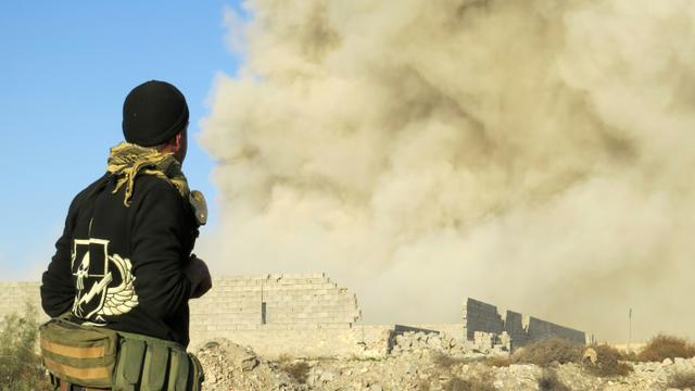 Un membre des forces progouvernementales irakiennes regarde la fumée s'élever de Ramadi, à 110 km à l'ouest de Bagdad, le 27 décembre 2015 [STR / AFP]
